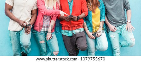 Group of friends watching smart mobile phone - Teenagers addiction to new technology trends - Youth lifestyle, tech, social, millennial generation and friendship concept - Main focus on center hands Royalty-Free Stock Photo #1079755670