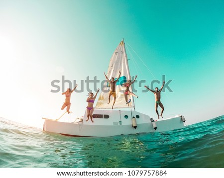 Happy crazy friends diving from sailing boat into the sea - Young people jumping inside ocean in summer vacation - Main focus on center guys - Travel and fun concept - Fisheye lens distortion #1079757884