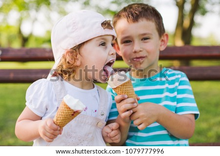Cute little boy share ice cream with his sister