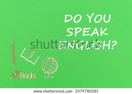 concept school for kids, text do you speak english, school supplies wooden miniatures on green backboard #1079780285