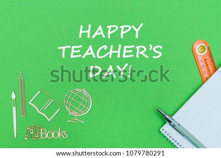 concept school, text happy teacher's day, school supplies, notebook, ruler and pen on green backboard #1079780291
