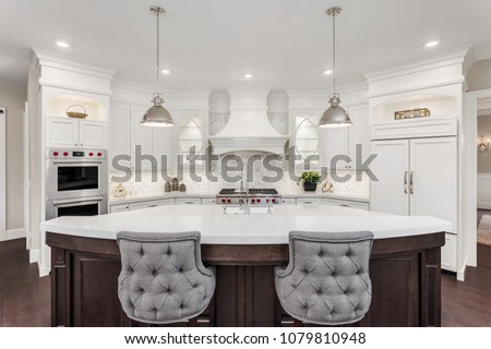 Beautiful Kitchen in Luxury Home with large island, refrigerator, pendant lights, double ovens, range, and hood.  Cabinets and Island are off-white. #1079810948