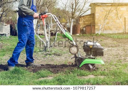 Man working in the spring garden with tiller machine. #1079817257