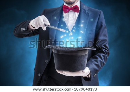 Magician or illusionist is showing magic trick. Blue stage light in background. #1079848193