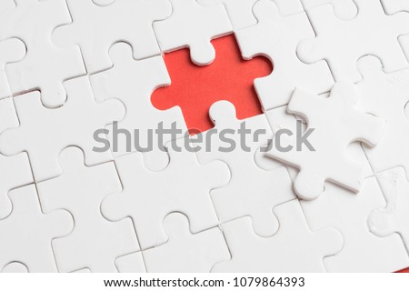 put the last piece of jigsaw puzzle to complete the mission on red background Royalty-Free Stock Photo #1079864393