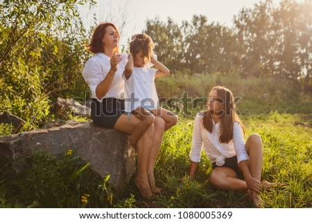 mom combs her daughter's hair in nature. Woman with two daughters sitting in the Park in the summer #1080005369