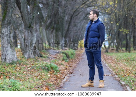Young beard man in a autumn park #1080039947