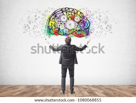 Rear view of a young successful businessman standing with hands in the air celebrating a business victory. A concrete wall background with a cog brain sketch on it. #1080068855