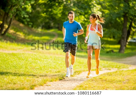 Young couple running in the park on the sunny day #1080116687