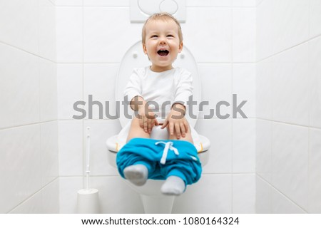 Excited two year old toddler sitting on toilet with pants down #1080164324