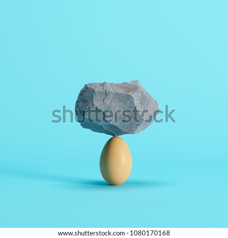 Stone put on Egg on blue background. minimal creative idea concept.