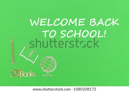 concept school for kids, text welcome back to school, school supplies wooden miniatures on green backboard #1080208172