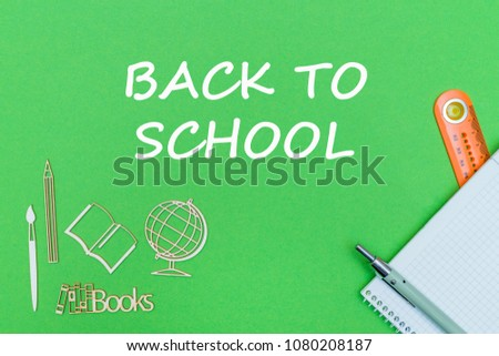 concept school, text back to school, school supplies, notebook, ruler and pen on green backboard #1080208187