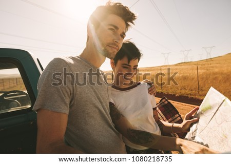 Couple looking at a map for navigation while on a road trip. Woman pointing at the map while the man looks away in the country side. #1080218735