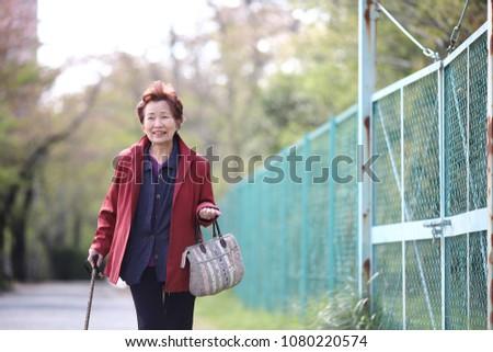 Senior woman walking outdoors #1080220574
