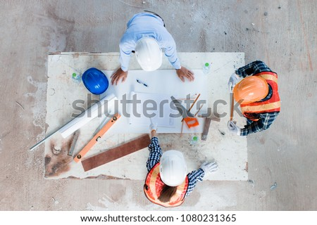 Team of young man and woman engineer and architects working, meeting, discussing,designing, planing, measuring layout of building blueprints in construction site floor at factory, top view. copy space #1080231365