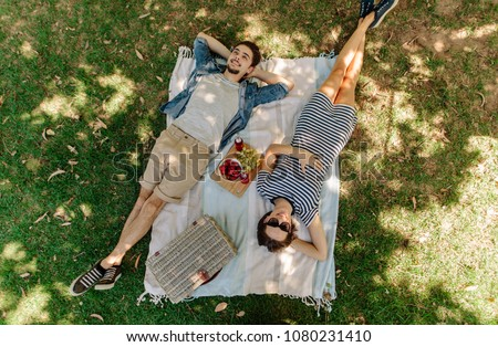 View from above of relaxed man and woman lying down at the park with hand basket, appetizing snacks and beers on blanket. Couple on picnic lying on blanket in grass outdoors. #1080231410
