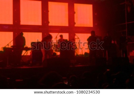 Blurred photo of red lights in a live concert on stage. #1080234530