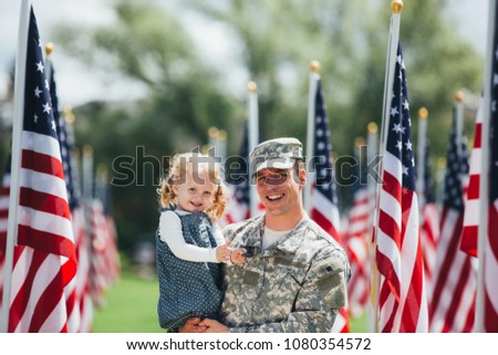 American Soldier father in uniform holding toddler daughter , smiling at the camera with American flags in the background