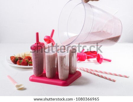 Summer food: cooking home-made fruit ice. Filling the prepared mass in ice cream molds. Royalty-Free Stock Photo #1080366965