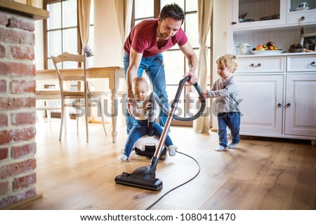 Father and two toddlers doing housework. #1080411470