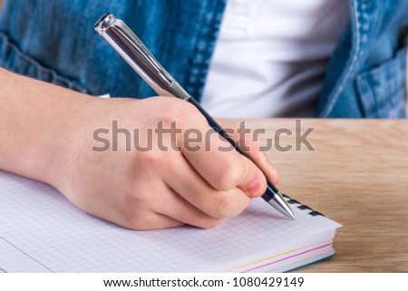 Child's hand holding pen. The child writing letters in a notebook. #1080429149