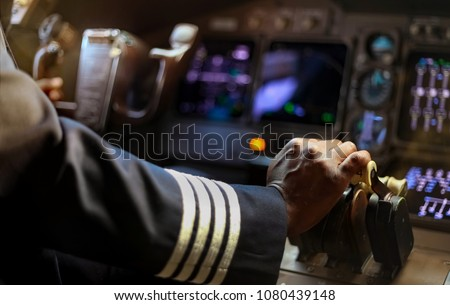 Cropped Hands of African Pilot flying a commercial airplane, cockpit view close up of hands #1080439148