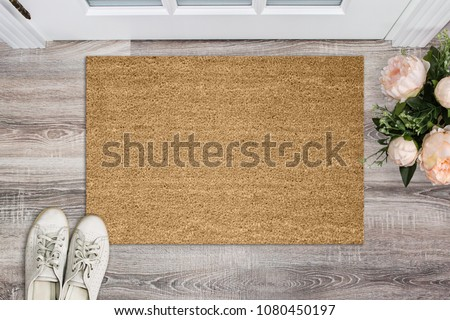 Blank coir doormat before the door in the hall. Mat on wooden floor, flowers and shoes. Welcome home, product Mockup Royalty-Free Stock Photo #1080450197