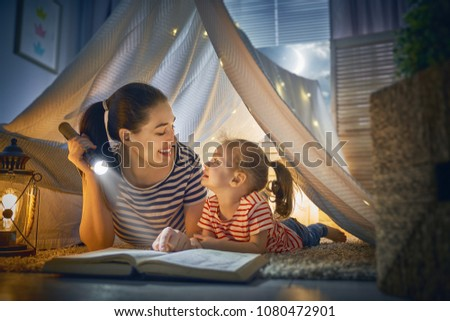 Family bedtime. Mom and child daughter are reading a book in tent. Pretty young mother and lovely girl having fun in children room. #1080472901