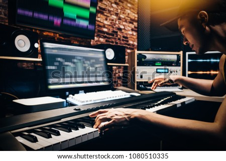 asian male music arranger hands composing song on midi piano & professional audio equipment in digital recording studio #1080510335