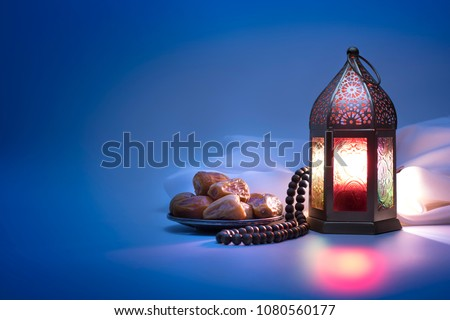 Low light photo of Lantern, Dates fruit and rosary beads for Ramadan and Eid greeting. #1080560177