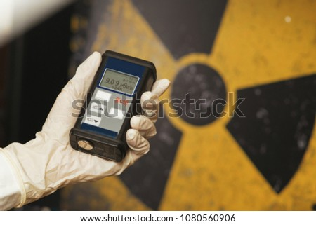 radiation supervisor with geiger counter checks the level of radioactive radiation in the danger zone #1080560906