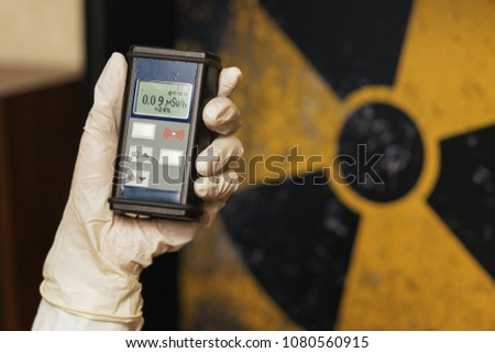 Radiation supervisor in glove with geiger counter checks the level of radiation in the radioactive zone #1080560915