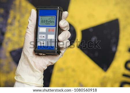 radiation supervisor with geiger counter checks the level of radioactive radiation in the danger zone #1080560918