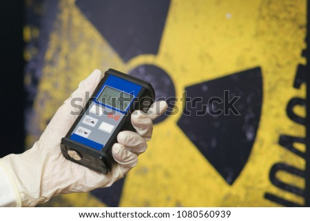 radiation supervisor with geiger counter checks the level of radioactive radiation in the danger zone #1080560939