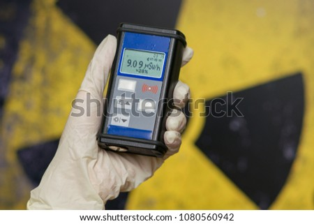 radiation supervisor with geiger counter checks the level of radioactive radiation in the danger zone #1080560942