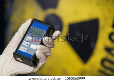 radiation supervisor with geiger counter checks the level of radioactive radiation in the danger zone #1080560999