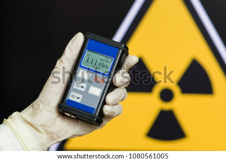 radiation supervisor with geiger counter checks the level of radioactive radiation in the danger zone #1080561005