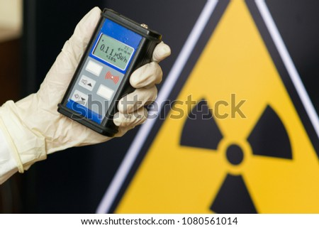 Radiation supervisor in glove with geiger counter checks the level of radiation in the radioactive zone #1080561014