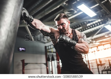 Bearded Male boxer training with punching bag in dark sports hall. Young tattoed boxer training on punching bag. Male boxer as exercise for the big fight. Boxer hits punching bag. #1080588539