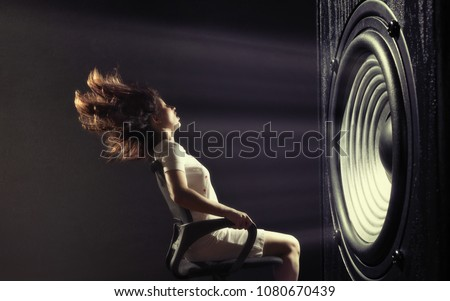 The powerful sound set back a young woman. Royalty-Free Stock Photo #1080670439