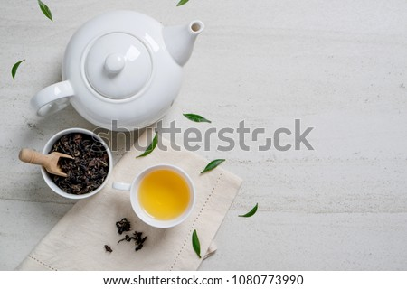Top view mockup a cup of tea and tea leaf on the white desk. Free space for your text. #1080773990