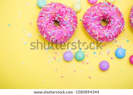 pink donuts with sprinkles on yellow background  #1080894344
