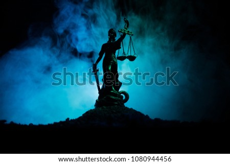 The Statue of Justice - lady justice or Iustitia / Justitia the Roman goddess of Justice on a dark fire background. Selective focus #1080944456