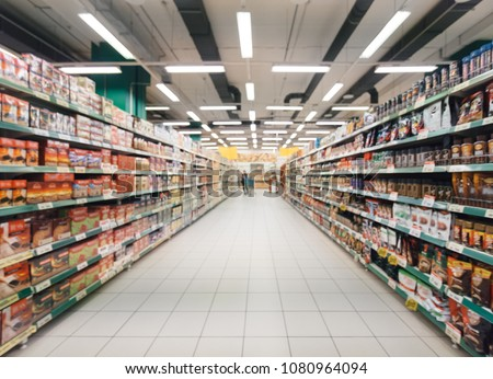 Abstract blurred supermarket aisle with colorful shelves and unrecognizable customers as background Royalty-Free Stock Photo #1080964094