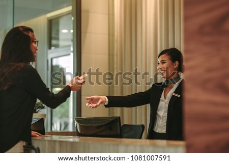Woman at reception giving her credit card to female receptionist for payment. Female guest paying for room in hotel. #1081007591