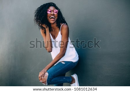 Portrait of a curly haired woman wearing fashionable clothes standing against a wall. Happy looking woman standing against a wall with arms crossed wearing sunglasses. #1081012634