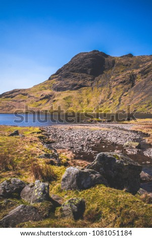 View of harrison stickle fell from the shore of Stickle Tarn / lake with rocks and grass in the foreground. #1081051184