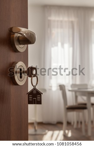 Open door to a new home. Door handle with key and home shaped keychain. Mortgage, investment, real estate, property and new home concept #1081058456
