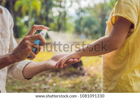 dad and son use mosquito spray.Spraying insect repellent on skin outdoor Royalty-Free Stock Photo #1081091330